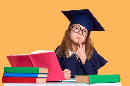 Diligent girl in glasses and graduation clothes thinking while sitting at desk with colourful books and pen over yellow background Stock fotó