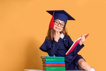 Excited smiling schoolgirl in glasses and graduation clothes cheering while sitting at desk with colourful books and pen over yellow background Stockfoto