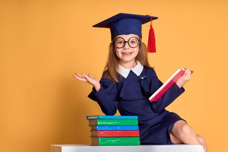 Excited smiling schoolgirl in glasses and graduation clothes cheering while sitting at desk with colourful books and pen over yellow background