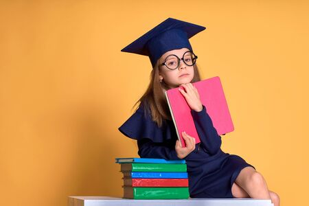 Thoughtful girl in glasses and graduation clothes thinking while sitting at desk with colourful books and notebook in hand over yellow background