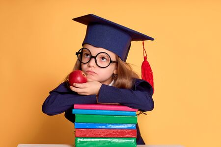 Thoughtful girl in glasses and graduation clothes thinking while lay down on the colourful books and holds an apple over yellow background Stockfoto