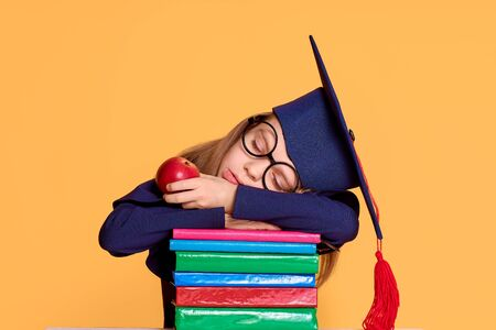 Cheerful schoolgirl in graduation outfit slepping while holding an apple on pile of colourful books over yellow background Stockfoto
