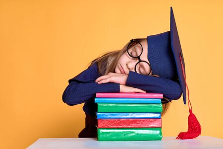 Cheerful schoolgirl in graduation outfit slepping on pile of colourful books over yellow background