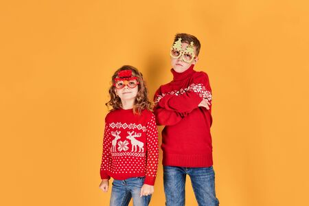 Confident children in warm red Christmas sweaters and decorated glasses looking at camera on yellow background