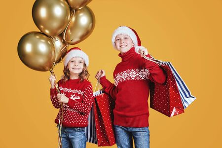 Cute children in red Santa hats and sweaters hugging and holding shopping bags and golden balloons on yellow background Stock Photo