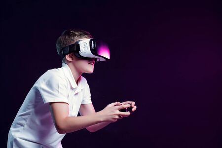 Side view of excited kid in white t-shirt and virtual reality headset standing bending forward playing with joystick on black background