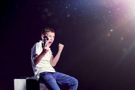 Side view of aggressive child with joystick screaming at heavens after losing clenching fist and looking up on black background