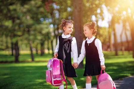 Portrait of happy Caucasian young smiling girls wearing school backpack outside the primary school. schoolgirl, elementary school student going from school, graduation, summer holidays. Reklamní fotografie