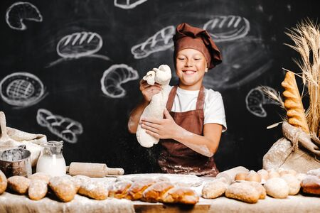 cute boy with chef hat and apron standing at table kneading bread dough and looking at camera, having fun.