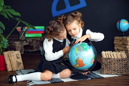 Little twin girls in school uniform using magnifying glass to examine globe while sitting on floor during geography lesson Reklamní fotografie