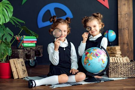 Little twins in school uniform smiling and looking at camera through magnifiers while examining globe during geography lesson