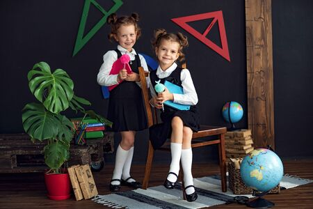 Little twins in school uniform holding books while studying together