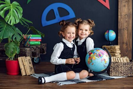 Little twins in school uniform smiling and looking at camera while examining globe during geography lesson Reklamní fotografie