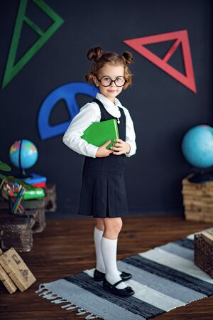 Clever little girl in school uniform and glasses smiling and looking at camera while holding green textbook before studies