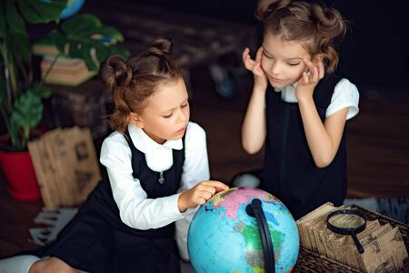 Little twin girls in school uniform examine globe while sitting on floor during geography lesson