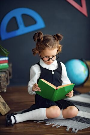 Clever little girl in school uniform and glasses holding, reading green textbook before studies Reklamní fotografie