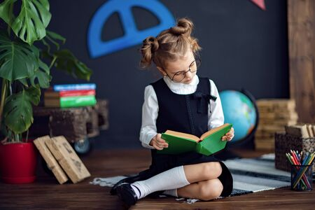 Clever little girl in school uniform and glasses reading green textbook before studies