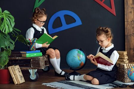 Little twins in school uniform and glasses reading interesting books while studying together