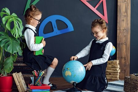 Little twins in school uniform and glasses reading interesting books, examine globe while sitting on floor while studying together
