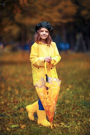 Happy funny child girl with umbrella in rubber boots at autumn park