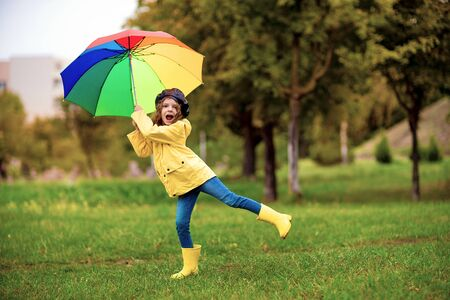 Happy funny child girl with multicolor umbrella in rubber boots at autumn park