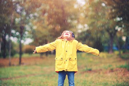 Adorable girl in yellow rain coat playing under the rain in the autumn park.