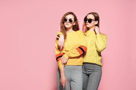 Two beautiful gorgeous girls standing in stylish yellow sweaters, gray pants, sunglasses on pink background