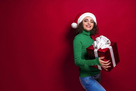Smiling woman in santa claus hat. Warm Christmas sweater holding gift box on. The concept of the gift. Emotions