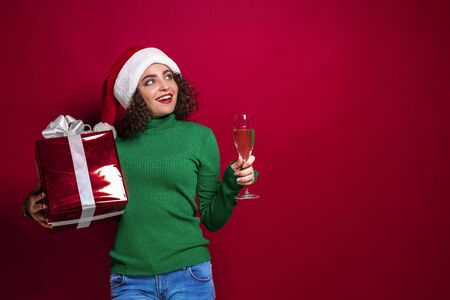 Beautiful fashion woman in santa claus hat, warm green Christmas sweater holding a glass of champagne and gift box on red background. The concept of the gift. Emotions Stok Fotoğraf