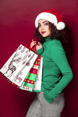 Beautiful fashion woman in santa claus hat. wearing bright Christmas carrying colorful shopping bags. The concept of the gift and christmas shopping.