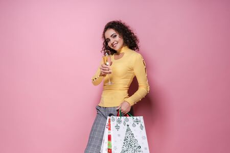 Beautiful women wearing bright Christmas carrying colorful shopping bags. On pink background. Christmas shopping And happy new year. discounts, sales at stores around the world. Black friday.