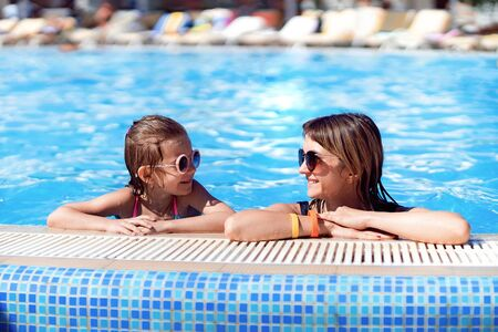 Happy family, young active mother and adorable little daughter having fun in a swimming pool enjoying summer vacation at a tropical resort.