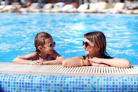 Szczęśliwa rodzina, młoda aktywna matka i urocza córeczka zabawy w basenie, ciesząc się letnimi wakacjami w tropikalnym kurorcie.
