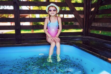 Young girl in hat, swimsuit receiving massage with small fishes. Peeling with fish. Girl enjoying medicinal procedure. Foot massage with fish in aquarium closeup. Fish spa procedure.