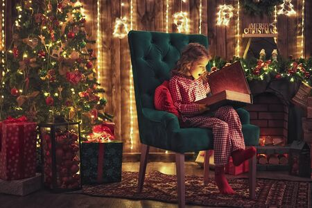 Happy holidays. Cute little child in pajama opening present near Christmas tree. The girl laughing and enjoying the gift.