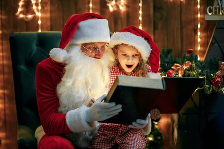 Santa Claus open and read magic book with little cute amazed girl in pajama and santa hat