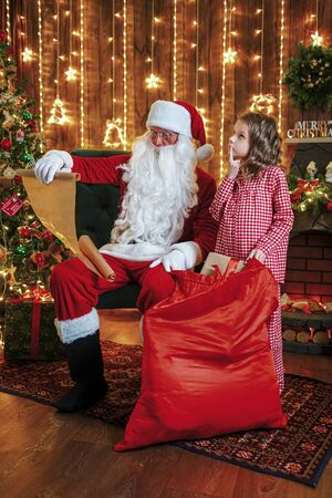Santa Claus with little cute amazed girl in pajama packing gifts at Santas home