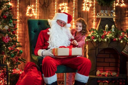 Little girl peeping from behind santa claus in his home when it sleep