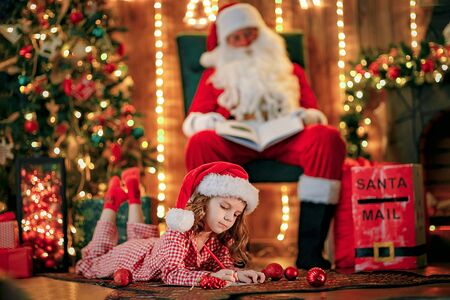Little charming girl in pajama, Santa hat is lying on the floor and writes a letter, draws with a pencil. lights of garlands. warm comfortable room