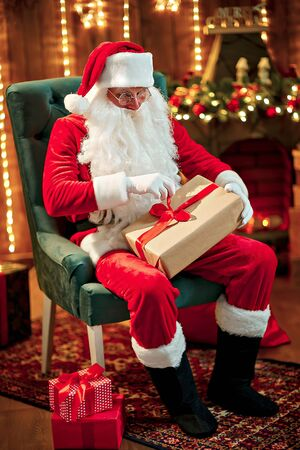 Photo of happy Santa Claus in eyeglasses sitting on chair, hold gift box.