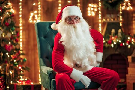Photo of happy Santa Claus in eyeglasses sitting on chair and looking at camera
