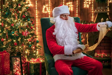 Portrait of happy Santa Claus sitting at his room at home near Christmas tree, fireplace and reading Christmas letter or wish list