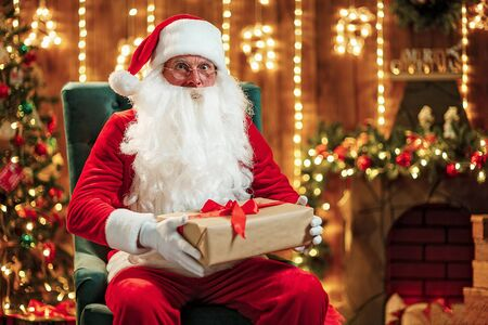 Photo of happy Santa Claus in eyeglasses sitting on chair, hold gift box and looking at camera Фото со стока