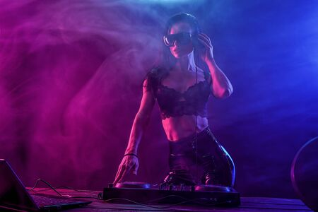 Young sexy woman dj in bra and sunglasses playing music. Headphones and dj mixer on table. Colorful Smoke on background