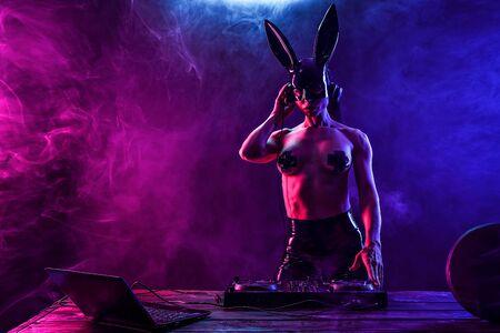 Young sexy woman dj playing music in mask, black nipple cross. Headphones and dj mixer on table. Smoke on background Фото со стока