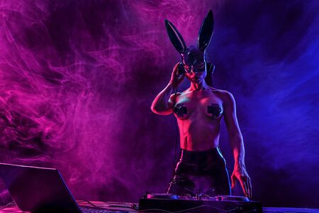 Young sexy woman dj playing music in mask, black nipple cross. Headphones and dj mixer on table. Smoke on background 免版税图像