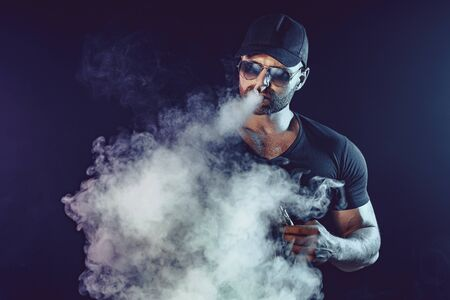Men with beard in sunglasses vaping and releases a cloud of vapor. Фото со стока