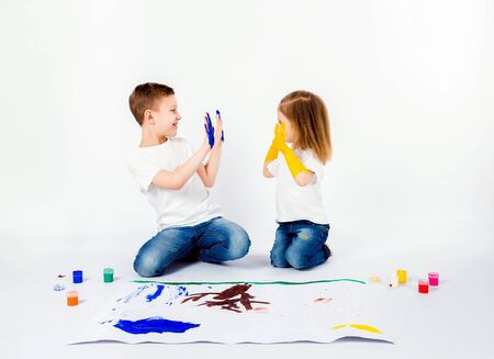 Two pretty child friends boy and girl in white shirts and blue jeans, trendy hair style, barefoot, drawing pictures on white sheet of paper by paints isolated on white. Shaking hands. Stockfoto - 134712595
