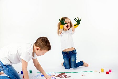 Two pretty child friends boy and girl in white shirts and blue jeans, trendy hair style, barefoot, drawing pictures on white sheet of paper by paints isolated on white. Showing hands in paint Stockfoto - 134712596