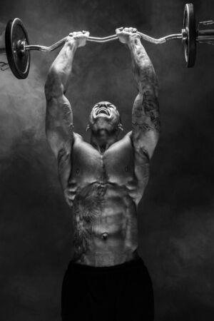Portrait d'un homme musclé soulevant des haltères. Prise de vue en studio. Exercice pour les triceps. Motivation.